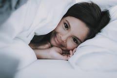 Meisje die onder Deken in Wit Bed liggen royalty-vrije stock afbeelding