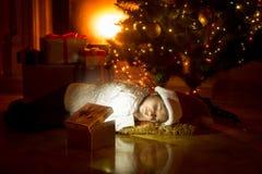 Meisje die onder Kerstboom liggen en in gloeiende giftdoos kijken Stock Fotografie