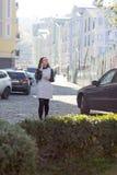 Meisje die onderaan de straat met haar telefoon lopen Stock Afbeelding