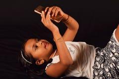 Meisje die op achter haar liggen en met haar mobiele telefoon, Pune spelen stock afbeelding