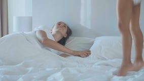 Meisje die op bed en kielzog omhoog haar jonge moeder in de vroege ochtend springen stock videobeelden