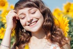 Meisje die op de achtergrond van zonnebloemgebied lachen royalty-vrije stock foto