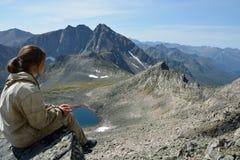Meisje die op de bovenkant van een klip, over de vallei en het meer kijken Stock Fotografie