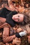 Meisje die op de de herfstbladeren liggen Royalty-vrije Stock Afbeelding