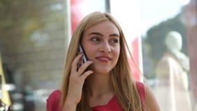 Meisje die op de kleding kijken en op haar mobiele telefoon op de achtergrond van winkelvensters spreken stock videobeelden