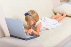 Meisje die op de laag met laptop leggen stock foto