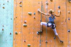 Meisje die op de muur beklimmen stock foto