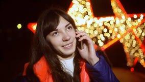 Meisje die op de nacht van telefoon bokeh smartphone spreken stock footage