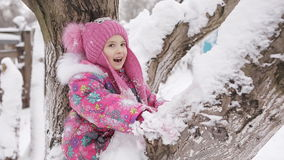 Meisje die op de snow-covered takken van bomen slingeren, stock footage