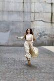 Meisje die op de straat op achtergrond van grijze muur lopen Royalty-vrije Stock Fotografie