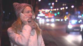 Meisje die op de telefoon in de avond op de straat spreken Kijk rond De auto's die overgaan door stock video