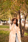 Meisje die op de telefoon in het de herfstpark spreken Stock Afbeelding