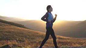 Meisje die op de weg in de bergen bij zonsondergang lopen, zonstraal stock footage