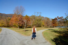 Meisje die op de weg, mooie de herfstdag lopen Royalty-vrije Stock Foto's