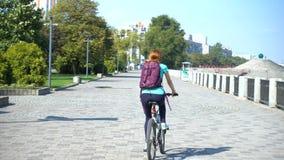 Meisje die op een fiets door de straten berijden stock videobeelden