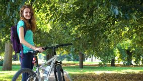 Meisje die op een fiets door de straten en bij het stadspark berijden stock video