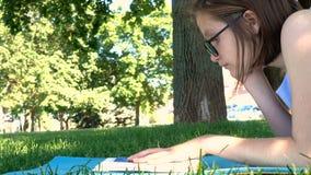 Meisje die op een gras bij het park liggen en een boek lezen stock video