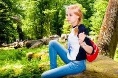 Meisje die op een grote rots rusten Stock Afbeeldingen