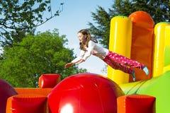 Meisje die op een Inflate Kasteel springen stock afbeeldingen