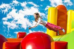 Meisje die op een Inflate Kasteel springen stock fotografie