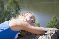 Meisje die op een rots liggen en rivier van mening genieten Stock Foto