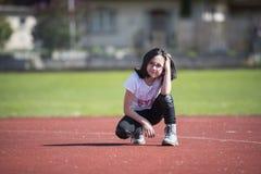Meisje die a op een sportenfaciliteit stellen Stock Foto's