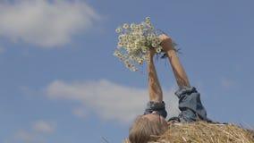 Meisje die op een stapel van stro met een boeket van margrieten liggen stock footage