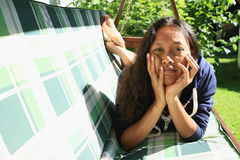 Meisje die op een tuinschommeling liggen Royalty-vrije Stock Afbeeldingen