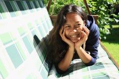 Meisje die op een tuinschommeling liggen Stock Foto's