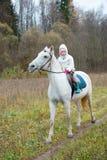 Meisje die op een wit paard berijden Stock Afbeelding