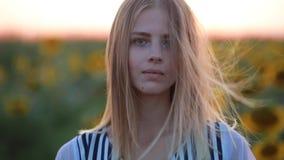 Meisje die op gebied bij zonsondergang camera, het haar van windslagen bekijken stock videobeelden