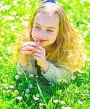 Meisje die op gras, grassplot op achtergrond liggen Gevoeligheidsconcept Het kind geniet de lente van zonnig weer terwijl het lig stock foto