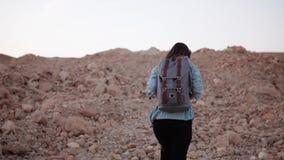 Meisje die op grote woestijnstenen wandelen Langzame Motie De vrouwelijke reiziger loopt omhoog de heuvel met grote rotsen moeili stock videobeelden