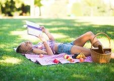 Meisje die op het gras en het lezen liggen royalty-vrije stock afbeeldingen