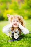 Meisje die op het gras liggen en haar oren behandelen niet om te horen stock fotografie
