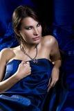 Meisje die op het linnen van het koningsblauwensatijn liggen stock foto