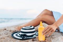 Meisje die op het strand, mooie gelooide benen tegen het blauwe overzees, kruik rusten room royalty-vrije stock foto's