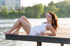 Meisje die op houten brug dichtbij de rivier liggen Royalty-vrije Stock Afbeeldingen