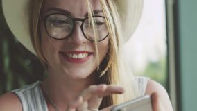 Meisje die op mobiele telefoon met vriend babbelen De vrouw schrijft massage op smartphone in koffie en het glimlachen stock footage