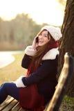 Meisje die op mobiele telefoon op bank in park spreken Stock Afbeeldingen