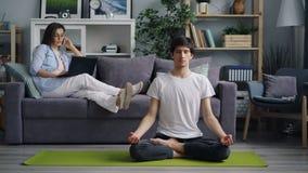 Meisje die op mobiele telefoon spreken die laptop met behulp van wanneer vriend die op yogamat mediteren stock videobeelden