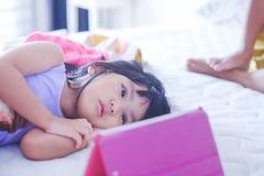 Meisje die op online video op tablet letten stock afbeeldingen