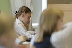 Meisje die op school aan leraar luisteren stock fotografie
