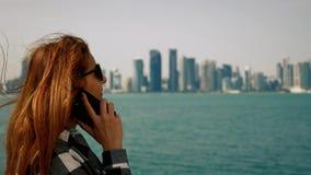 Meisje die op smartphone met Doha-wolkenkrabbers op achtergrond spreken stock video