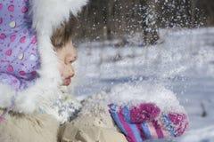 Meisje die op sneeuw blazen Stock Foto