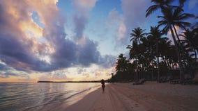Meisje die op tropisch strand vroeg in de ochtend lopen Zonsopgang over Caraïbische eilanddominicaanse republiek stock footage