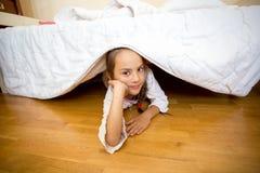Meisje die op vloer onder bed liggen stock afbeeldingen