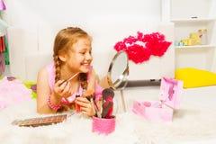 Meisje die op wit tapijt leggen en lipgloss toepassen Royalty-vrije Stock Afbeeldingen