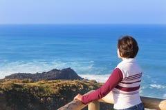 Meisje die op zee mening met bergen en water kijken. Portugal. Stock Fotografie
