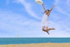 Meisje die over het water bij het strand springen Stock Afbeeldingen